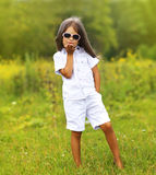 Stylish little girl in sunglasses. Posing outdoors Stock Photo