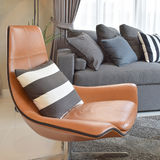 Stylish living room with black striped pillow on brown leather chair Stock Photos