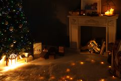 Stylish living room interior with Christmas lights and fireplace. At night royalty free stock photo