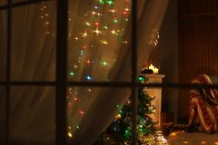 Stylish living room interior with Christmas lights at night. View through window stock photo