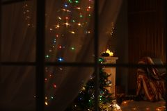 Stylish living room interior with Christmas lights. At night, view through window stock photos