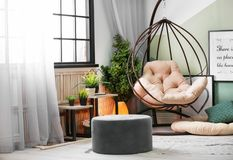 Stylish living room interior with comfortable   armchair. Stylish living room interior with comfortable hanging armchair Royalty Free Stock Images