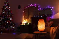 Stylish living room interior with lamp and Christmas lights. At night royalty free stock photography