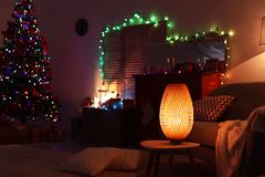 Stylish living room interior with lamp and Christmas lights. At night royalty free stock photos