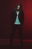 Stylish long haired man posing in studio. Handsome stylish long haired man posing in studio Royalty Free Stock Photo