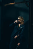 Stylish long haired man in suit drinking whiskey on black Royalty Free Stock Photography