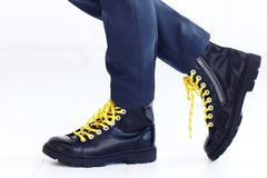 Stylish look of patent leather ankle boots with yellow shoelaces and socks at young boy. Kid Royalty Free Stock Photo