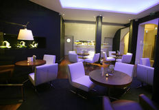 Stylish lounge bar. With white chairs and ambient lighting Royalty Free Stock Images