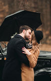 Stylish Loving wedding couple kissing and hugging in a pine forest near retro car Royalty Free Stock Images
