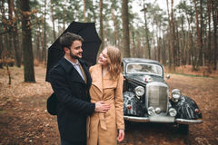 Stylish Loving wedding couple kissing and hugging in a pine forest near retro car Royalty Free Stock Photo