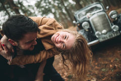 Stylish Loving wedding couple kissing and hugging in a pine forest near retro car Stock Photo