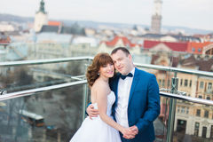 Stylish luxury bride and elegant groom hugging with tenderness on background of the old city Lviv Royalty Free Stock Photos