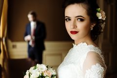 Stylish luxury bride and handsome elegant groom on the backgrou. Nd of rich interior in old building royalty free stock images