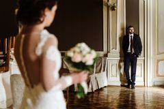 Stylish luxury bride and handsome elegant groom posing on the ba. Ckground of rich interior in old building royalty free stock photo