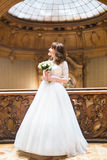 Stylish luxury bride posing with bouquet on the background of rich interior in old building Royalty Free Stock Image
