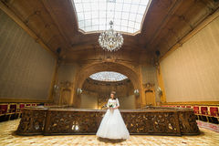 Stylish luxury bride posing with bouquet on the background of rich interior in old building Stock Photo