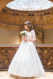 Stylish luxury bride posing with bouquet on the background of rich interior in old building Royalty Free Stock Images