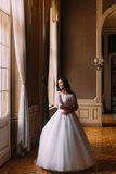 Stylish luxury bride posing near window with background of rich interior in old vintage building Stock Photography