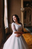 Stylish luxury bride posing in window light at background of rich interior in old vintage building Stock Photos