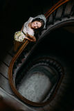 Stylish luxury bride in white dress with bouquet looking up posing on old wooden stairs, top view Stock Photo