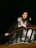 Stylish luxury bride in white dress looking up posing on old wooden stairs, top view Stock Images