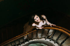 Stylish luxury bride in white dress looking up posing on old wooden stairs, top view Royalty Free Stock Images