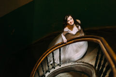 Stylish luxury bride in white dress looking up posing on old wooden stairs, top view Stock Image