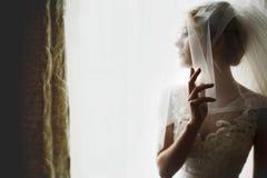 Stylish luxury gorgeous blonde bride posing on the background ho. Tel room stock photos