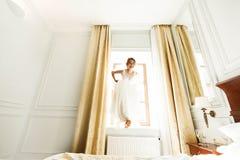 Stylish luxury gorgeous blonde bride posing on the background ho. Tel room royalty free stock photo