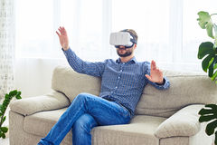 Stylish male with beard working in VR glasses sitting on sofa. Wide shot of stylish male with beard working in VR glasses sitting on sofa Royalty Free Stock Photography