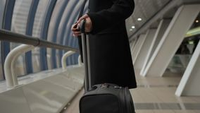 Stylish male brunette in black coat is holding suitcase handle in airport. Passenger in strict clothing after flight announcement goes to exit and pulls stock footage