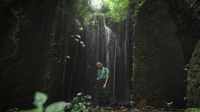 Stylish male explorer resting on a rock in cave near a waterfall behind him. Young man standing in bay inside the. Stylish male explorer is resting on a large stock video