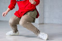 Stylish male hip-hop dancer in action. Trendy guy dancing break dance on grey background. Street style dancing Royalty Free Stock Image