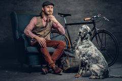 Stylish male with long hair posing with Ireland setter and singl. E speed bicycle stock image