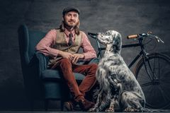 Stylish male with long hair posing with Ireland setter and singl. E speed bicycle royalty free stock photo