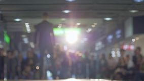 Stylish male model in solid costume and shoes walk the podium during fashion show on background blurred audience