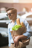 Stylish male pedestrian shopping. Healthy food. Young man in selective focus outdoors, modern hipster Royalty Free Stock Photography