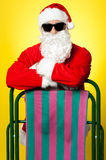 Stylish male santa posing with a deckchair Royalty Free Stock Photography