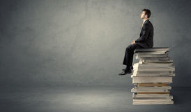 Stylish male seated on books. A serious student in elegant suit sitting on a stack of books in front of dark grey background Royalty Free Stock Photo