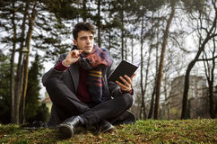 Stylish male student holding notebook and thinking. Sitting on grass in park. On autumn Stock Photos