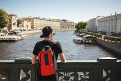 Stylish male tourist with backpack looking to cityscape on the embankment of Griboyedov canal in St. Petersburg, Russia.  Stock Images