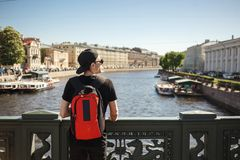 Stylish male tourist with backpack looking to cityscape on the embankment of Griboyedov canal in St. Petersburg, Russia.  Royalty Free Stock Photo