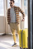 Stylish male tourist in sunglasses with wheeled bag. At subway exit Royalty Free Stock Photo
