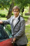 Stylish man. Beauty young man in new coat, gray jeans and white sweater is standing near the car in the forest Stock Photography