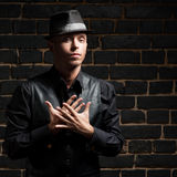 Stylish man against black brick wall. Young stylish caucasian man in black shirt and hat against black brick wall Royalty Free Stock Photos