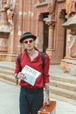 Stylish man with backpack travel newspaper and vintage suitcase walking. In city stock photo