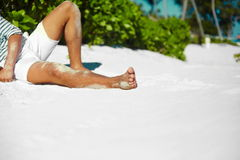 Stylish man on beach sand in sun glasses. Stylish young male model man body lying on beach sand  wearing hipster cloth enjoying summer travel holiday near ocean Royalty Free Stock Photography