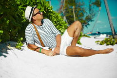 Stylish man on beach sand in sun glasses. Stylish young male model man lying on beach sand  wearing hipster summer hat  enjoying summer travel holiday near ocean Stock Images