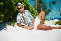 Stylish man on beach sand in sun glasses. Stylish young male model man lying on beach sand  wearing hipster summer hat  enjoying summer travel holiday near ocean Royalty Free Stock Photos