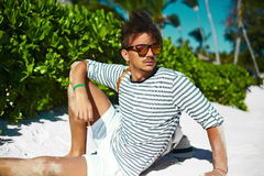 Stylish man on beach sand in sun glasses. Stylish young male model man lying on beach sand  wearing hipster summer hat  enjoying summer travel holiday near ocean Royalty Free Stock Images